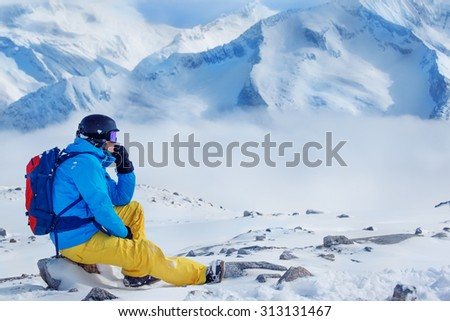 Snowboarder in helmet and goggles, with backpack looking at the mountains - stock photo