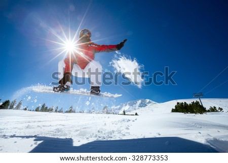 Snowboarder in the air with beautiful  blue sky in background - stock photo