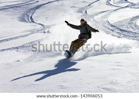 Snowboarder is having fun in the backcountry powder in the Italian Alps - stock photo