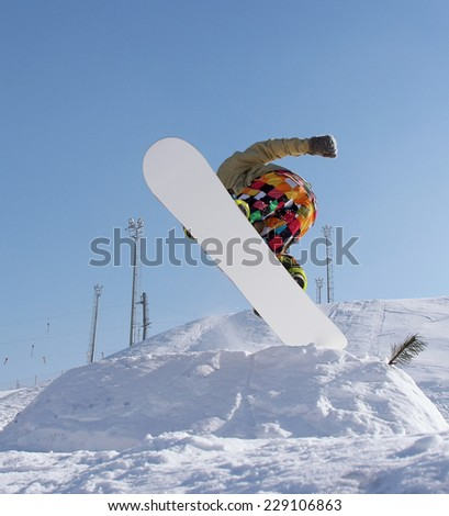 Snowboarder jumping against blue sky background - stock photo