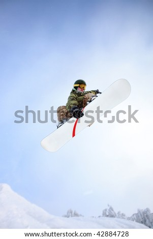 Snowboarder jumping through air with blue sky. - stock photo