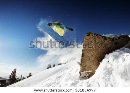 Snowboarder jumps from big rock. Sheregesh resort, Siberia, Russia - stock photo