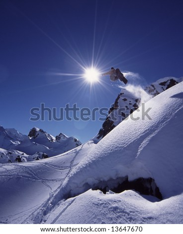 Snowboarder jumps high in dramatic mountain scene with white snow and clear blue sky. - stock photo