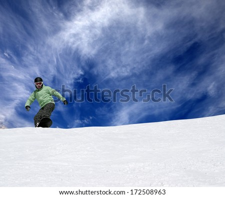 Snowboarder on off-piste slope and blue sky with clouds - stock photo