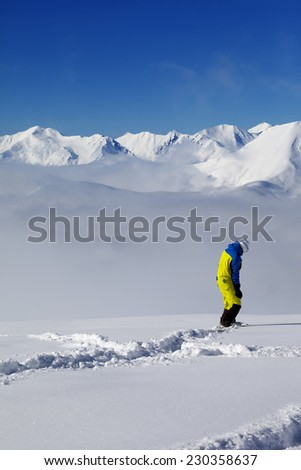 Snowboarder on off-piste slope with new fallen snow. Caucasus Mountains, Georgia, ski resort Gudauri. - stock photo