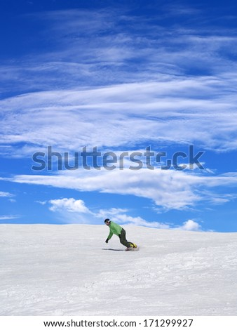 Snowboarder on ski slope and blue sky with clouds in nice day - stock photo