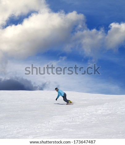 Snowboarder on ski slope and blue sky with clouds in sun day - stock photo