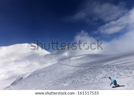 Snowboarder on ski slope at nice day - stock photo