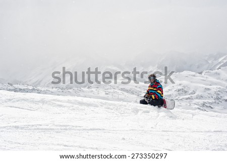 Snowboarder sit at top of mountain. Winter Scenic in the French Alps, Les 2 Alpes - stock photo