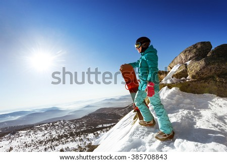 Snowboarder stands on valley and mountains backdrop. Space for text. Sheregesh resort, Siberia, Russia - stock photo