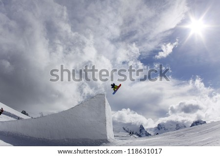 snowboarder taking big air jump with cloudy sky - stock photo