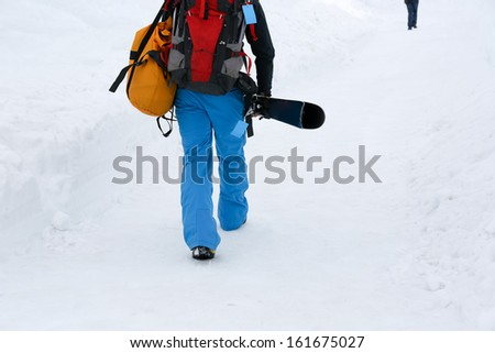 Snowboarders climbing to mountain top to start snowboarding - stock photo