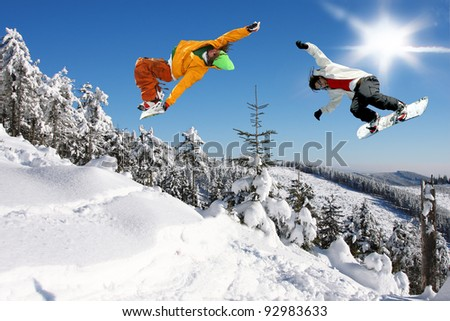 Snowboarders jumping against blue sky - stock photo