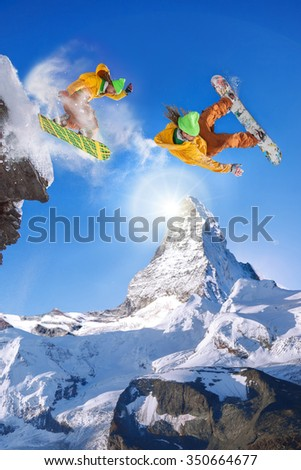 Snowboarders jumping against Matterhorn peak in Switzerland - stock photo