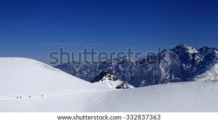 Snowboarders move on footpath to off piste slope at sun day. Caucasus Mountains, Georgia, ski resort Gudauri. - stock photo