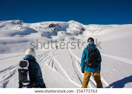 Snowboarders waiting for their friend during free-ride off-piste run on snowy mountain  - stock photo