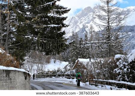 Snowboarders walk through the streets of a quaint alpine village near a ski resort in the Swiss Alps, Switzerland. - stock photo