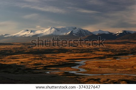 Snowcapped mountain peaks above orange steppe with whitewater river.  Altai mountains  Plato Ukok Siberia Russia - stock photo