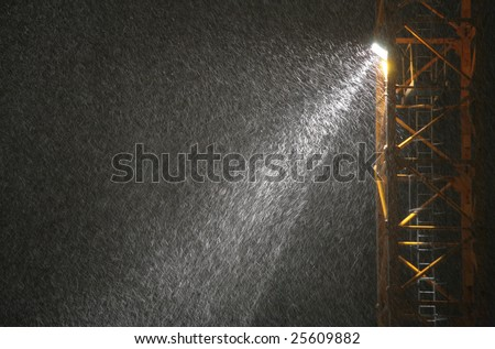 Snowfall in beam of projector at night - stock photo