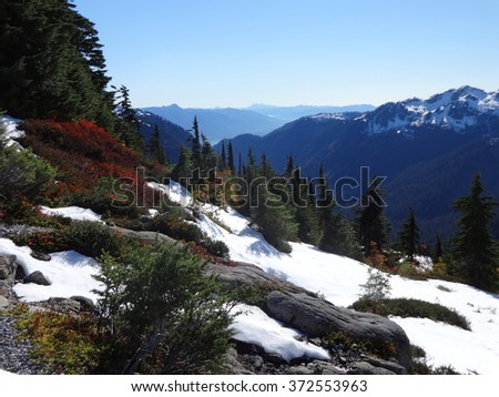 Snowfall on the mountains before the autumn colors ended  - stock photo