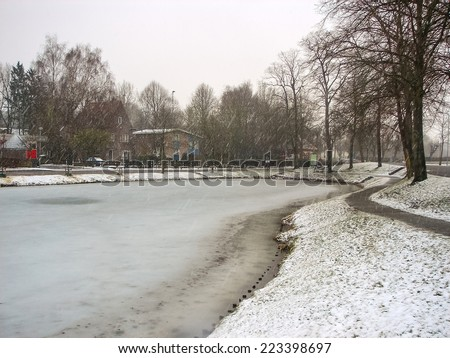 Snowfall on winter lake in the Dutch city Heerlen. Netherlands - stock photo