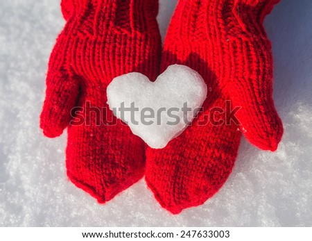 snowflake in the form of heart on red mittens - stock photo