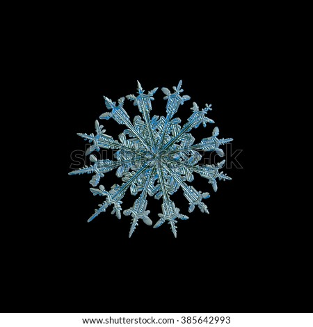 Snowflake isolated on black background for design. This is real snowflake macro photo (rare 12-sided snow crystal), captured on glass with LED back light. - stock photo