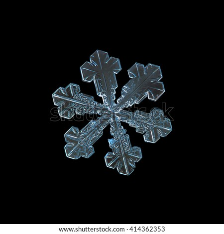 Snowflake isolated on black background: macro photo of real snow crystal, captured on dark woolen fabric in natural light. This is large snowflake of split plate type with simple shape. - stock photo