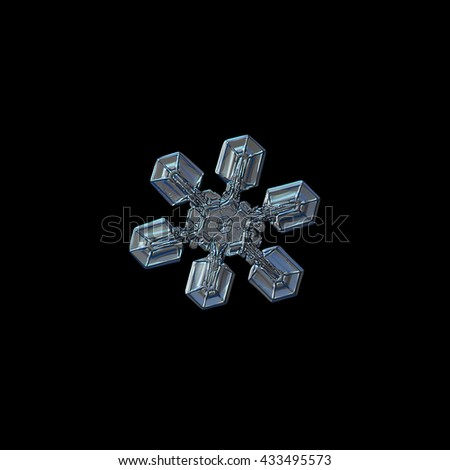 Snowflake isolated on black background: real photo of medium size snow crystal (around 3 millimeters from tip to tip), resembling gecko's paw, captured on glass surface with LED back light. - stock photo