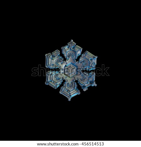 Snowflake isolated on black background. This is macro photo of real snow crystal with six broad arms and frozen bubbles of rime on glossy surface. Snowflake was captured on glass with back lighting. - stock photo