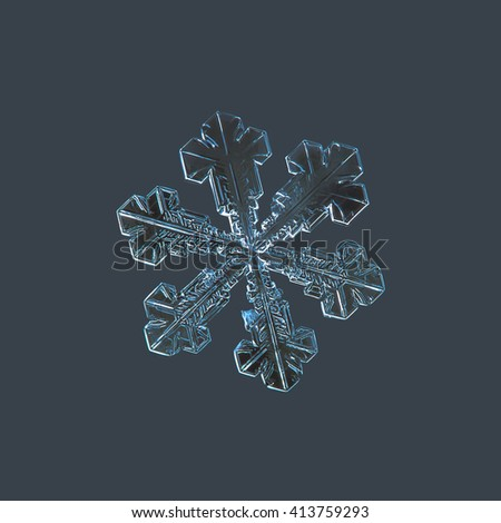 Snowflake isolated on dark cyan background: macro photo of real snow crystal, captured on glass surface with LED back light. This is large snowflake with broad arms and relatively simple structure. - stock photo