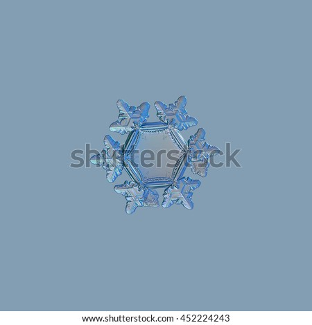 Snowflake isolated on pale blue background. This is macro photo of real snow crystal with unusually big, flat and empty central hexagon, and highly detailed outer rim and short arms with ridges. - stock photo
