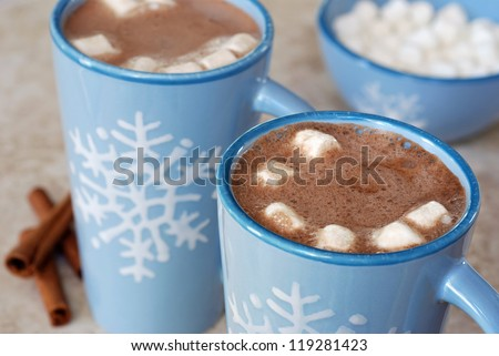Snowflake mugs filled with hot chocolate and marshmallows on tile counter with cinnamon sticks along side.  Matching bowl with marshmallows in soft focus in background.  Closeup with shallow dof. - stock photo