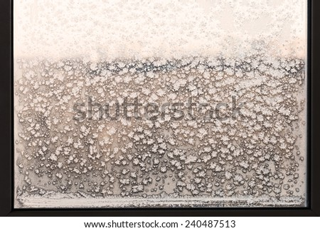 snowflakes and frost pattern on frozen home window in cold winter day - stock photo