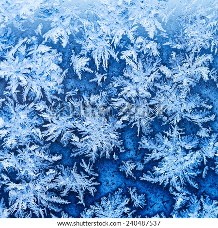 snowflakes and frost pattern on window glass in cold winter evening close up - stock photo
