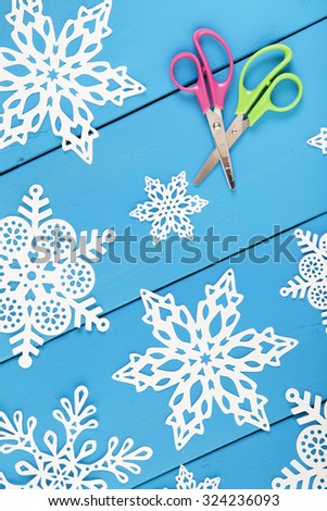 Snowflakes cut from paper.  A traditional Christmas arts and crafts project. - stock photo