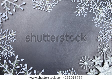 Snowflakes on a chalkboard. Christmas frame. - stock photo
