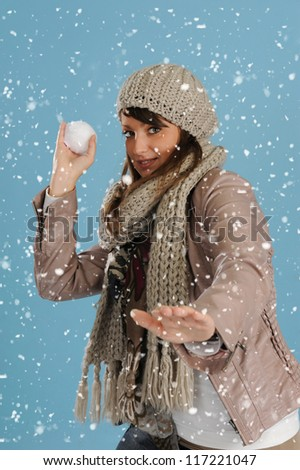 snowing on a  woman throwing a snow ball - stock photo