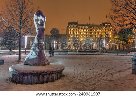 Snowing winter night on the Quai d'Ouchy in Lausanne, Switzerland featuring a statue and one of the luxury hotels in the background. - stock photo