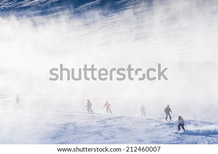 snowmakers blowing fresh snow on ski slopes - stock photo