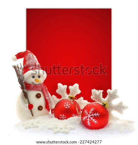 Snowman and Christmas ornaments in front of a red paper card - stock photo
