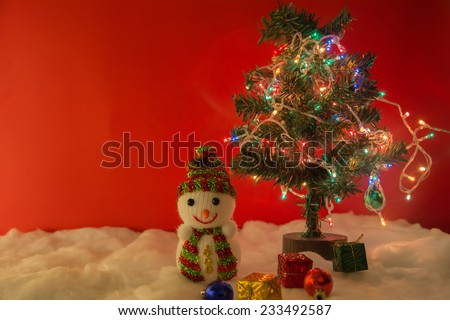 Snowman and christmas tree with LED light on white snow on red background, concept christmas night - stock photo