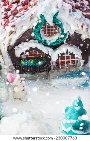 snowman and gingerbread house of sweets for Christmas. Focus on the snowman - stock photo