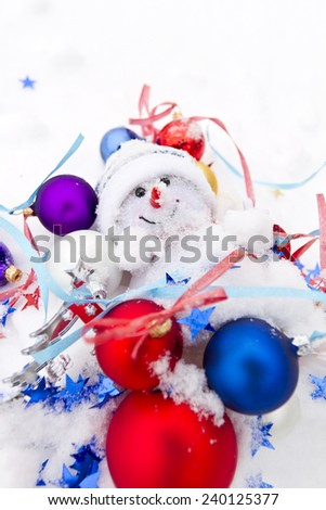 Snowman and multicolored Christmas balls in the snow - stock photo