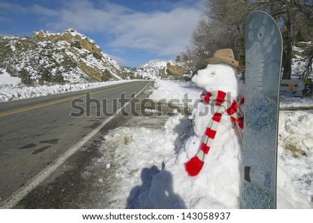 Snowman and snowboard in fresh snowfall along Highway 33 north of Ojai, California - stock photo