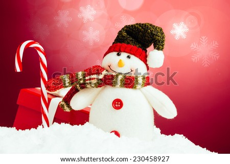 Snowman, christmas present and candy cane on a red background with snowflakes.  - stock photo