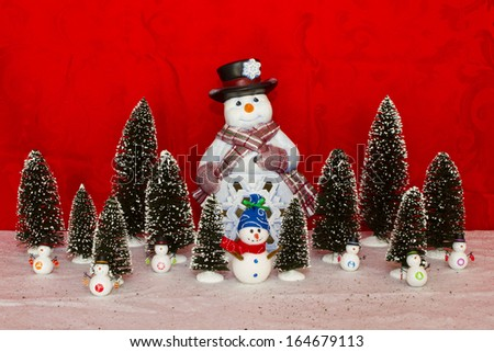 Snowman in a black hat and scarf with little snowman and trees - stock photo