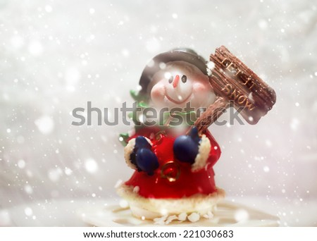 "Snowman in snowfall with plate ""Let it snow!"". Christmas greeting card. - stock photo"