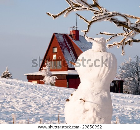 Snowman in the background house - stock photo