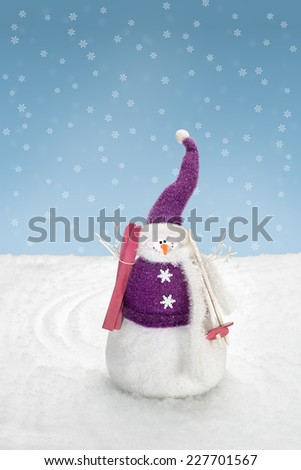 Snowman is standing in the snow with skis - stock photo
